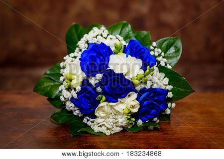 Bouquet with white and blue roses on brown background