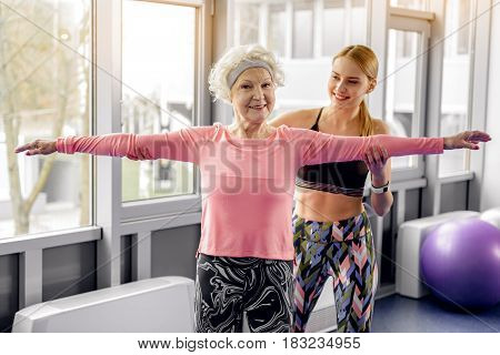 Cheerful woman training happy female retiree in modern gym. Granny making exercises in room
