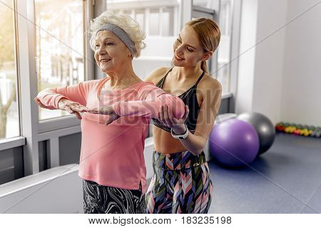 Hold your arms in one line. Female retiree expressing happiness while taking stance. Outgoing young woman helping beneficiary in fitness center
