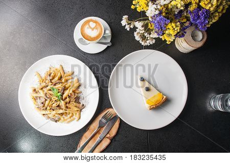 Top View Vegeterian Tasty Dinner - Creamy Mushroom Penne Pasta, Cup Of Coffee And Fruit Cheesecake O