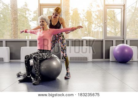Stretch out your arms. Outgoing young female describing how to do exercises to serene grandmother in fitness center