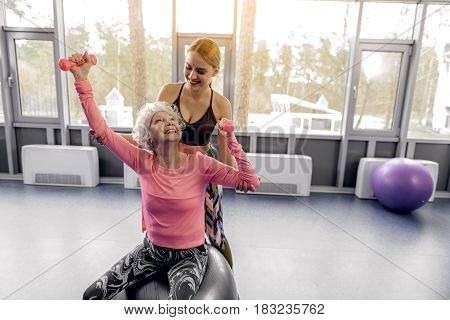 Grandma expressing happiness while raising arms with dumbbells while sitting on fitball in gym. Smiling woman helping her