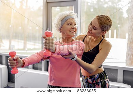 You do all in right way. Cheerful woman helping making exercises to beaming grandmother in gym