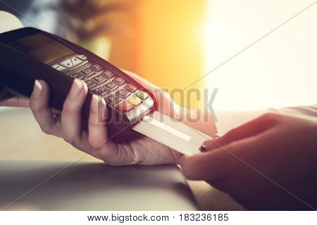 Woman placing credit card into reader closeup picture