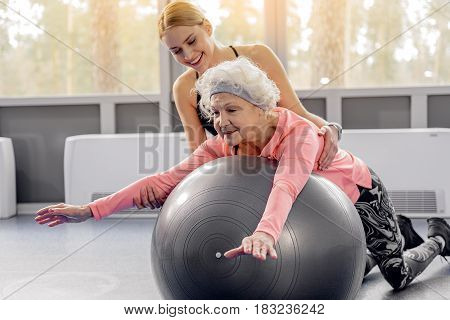 Cheerful grandmother making exercises in gym. Outgoing young female helping her in gym
