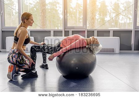 Cheerful coach training smiling grandmother. Happy granny engaging fitness in workout room