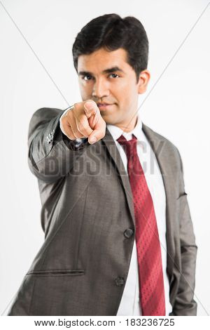 I want you concept - young indian businessman choosing you by pointing index finger at camera or you, standing isolated over white background