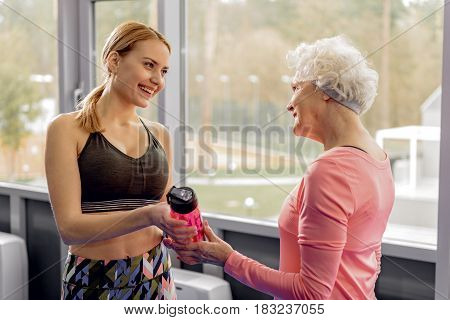 Outgoing young woman giving shaker to beaming grandmother after good training in fitness center