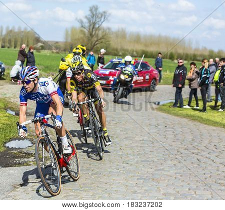 Hornaing France - April 102016: Group of cyclists riding in the peloton on a paved road in Hornaing France during Paris Roubaix on 10 April 2016.