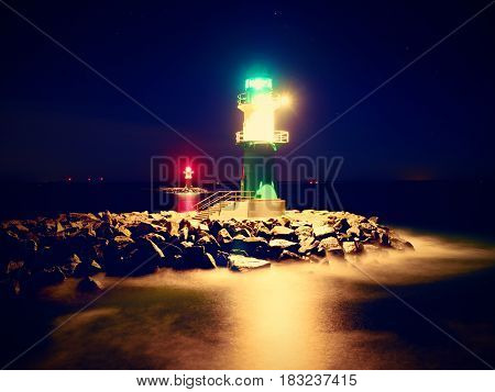 The ighthouse shinning at port gate. Modern light house at the end of stony pier in the dark night. Warnemunde on the Baltic Sea at the harbor entrance Germany