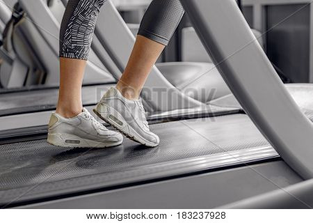 Focus on feet of female in trainers. She doing exercises on technical equipment in fitness center. close up