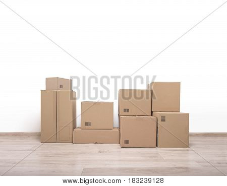 Empty room with a white wall and cardboard boxes on the floor.