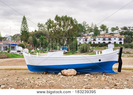The boat are aground in shallow sea water. Ship run aground in waterless pier or harbor