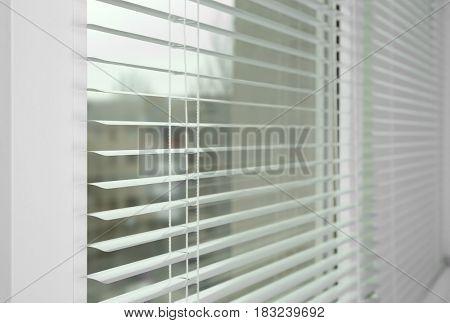 Window with white jalousie, closeup