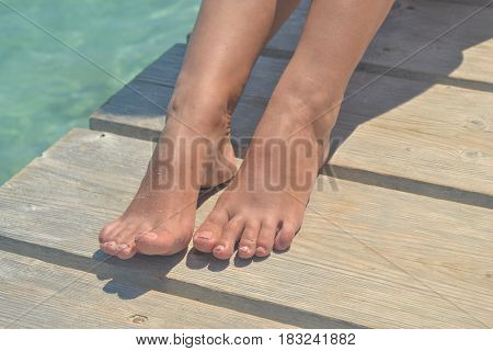 Tanned well-groomed legs with a nude-style pedicure on a turquoise sea background.