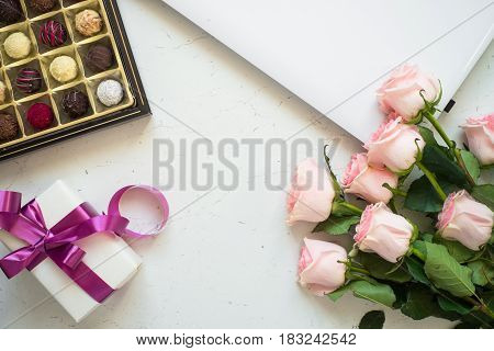 Pink rose notebook present and truffle at white stone table. Top view copy space. Work and holiday