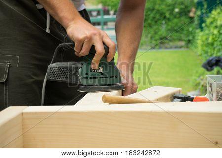 Man sanding wooden board DIY project in garden