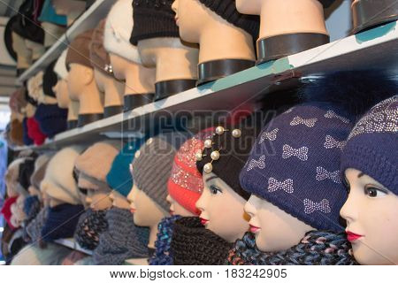A variety of female winter knitted hats on mannequin heads. Colorful hand knitted hats sale