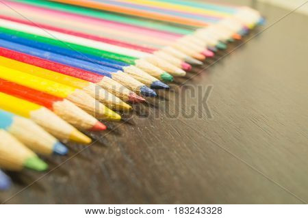 Colored pencils colors of rainbow on a wooden board diagonal