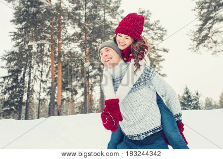 Love - Happy couple having fun smiling laughing together on romantic holidays. Young man giving piggyback ride to his girlfriend outdoor in winter park