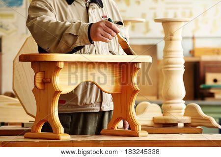 Carpenter varnishing a wooden bench using paintbrush in his workshop
