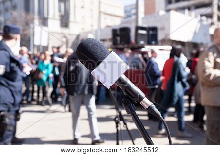Protest. Demonstration. Microphone in focus, blurred protesters in background.