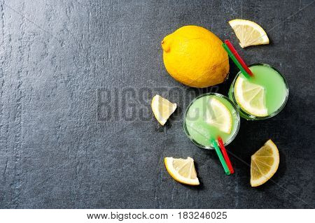 Cold cocktail with lime lemon, tonic, vodka and ice on dark background top view with copyspace