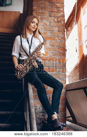 Young Attractive Girl Sitting On Handrail In White Shirt With A Saxophone - Outdoor. Sexy Young Woma