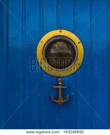 Stylish door with a bull's eye and an anchor-shaped knocker an interesting door in a seaside village a blue door