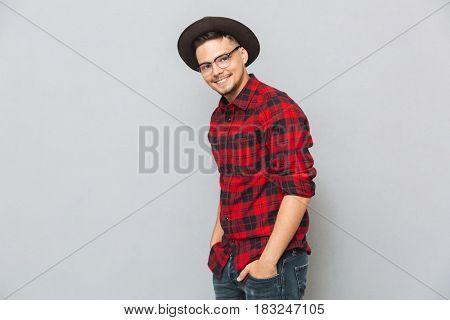 Smiling asian man holding his hands in pockets while posing at camera