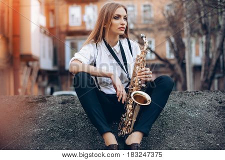 Young Attractive Girl In White Shirt With A Saxophone Sitting Sits On The Earth - Outdoor. Sexy Youn