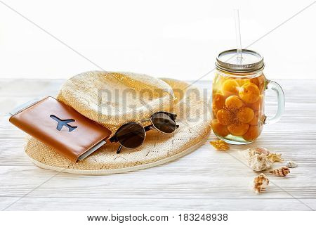 summer vacation concept. yellow cocktail juice with apricot hat sunglasses and shells and passport on white rustic wooden background in light. space for text. travel and summer holiday
