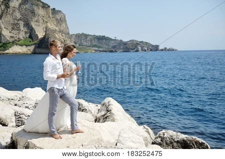 Happy young couple in wedding day with champagne glass near sea Naples Italy