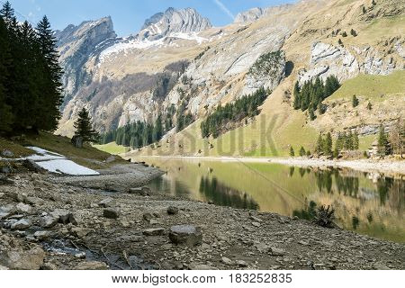 Tranquil scene of lake of seealpsee reflecting the mountain in Alpstein Switzerland