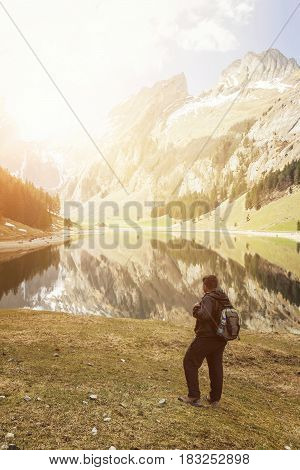back of hiker with backpack who watching to the lake and mountains of Seealpsee Switzerland