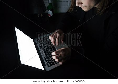 Cropped picture of young serious man using laptop computer at home indoors at night.