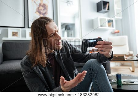 Image of young confused man sitting at home indoors play games with joystick. Looking aside.