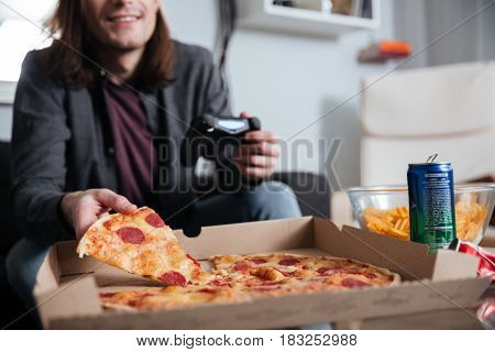 Cropped image of young man gamer sitting at home indoors and play games with joystick while eating.