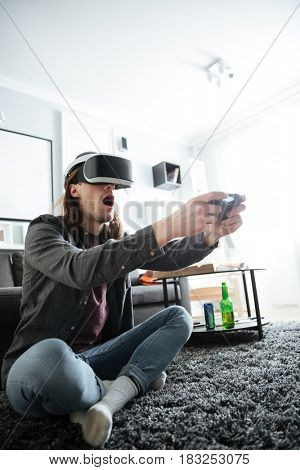 Picture of young concentrated man sitting at home indoors play games with 3d virtual reality glasses. Looking aside.