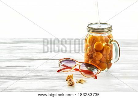 Summer Vacation Concept. Yellow Cocktail Juice With Apricot,  Sunglasses And Shells In Light On Whit