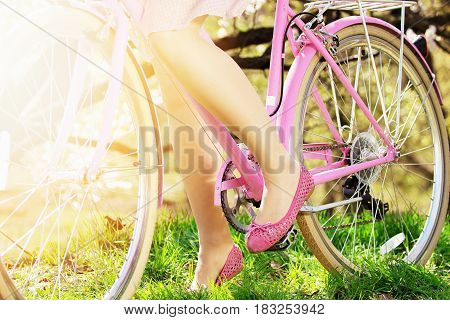 Vintage Bike Concept. Closeup Of Tender Legs Of Young Beautiful Girl Standing On Pedals Of Retro Bik