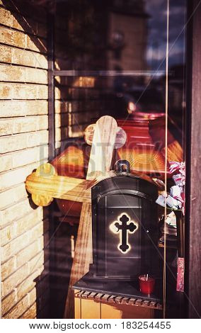 In front of shop window of funeral equipment in style of christian tradition.