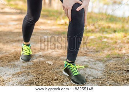 Girl In Sports Pants And Shoes, Standing Holding On To The Knee, On The Nature. Knee Injury