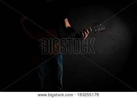 The Guitarist In Jeans Plays An Acoustic Guitar, On The Left Side Of The Frame, On A Black Backgroun