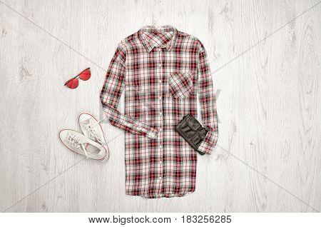 Checkered female shirt black handbag white sneakers glasses. Fashionable concept wooden background