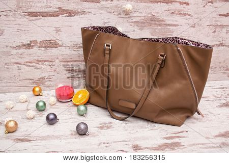 Big brown ladies handbag on a wooden background Christmas ornaments garland and candle. fashion concept