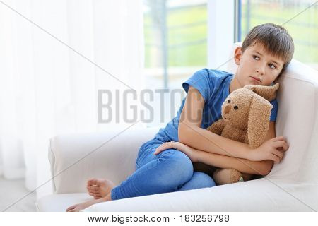 Sad little boy sitting in armchair at home