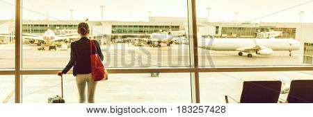 Traveler businesswoman at airport banner. Travel lifestyle. Woman waiting for delayed flight at airport lounge standing with luggage watching sunset at airport window. Panorama crop.