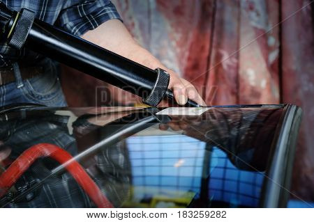Repair and replacement of the windshield. Car mechaniс is putting a black sealant to a windshield.
