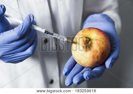 Doctor or scientist makes hyaluronic acid rejuvenation beauty injections to a red yellow rotten apple. Beautician shows that hyaluronic acid is healthy natural and full of vitamins good for faceskin.